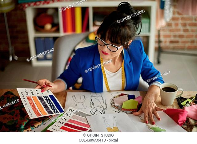Woman in design studio sitting at desk looking at colour swatches