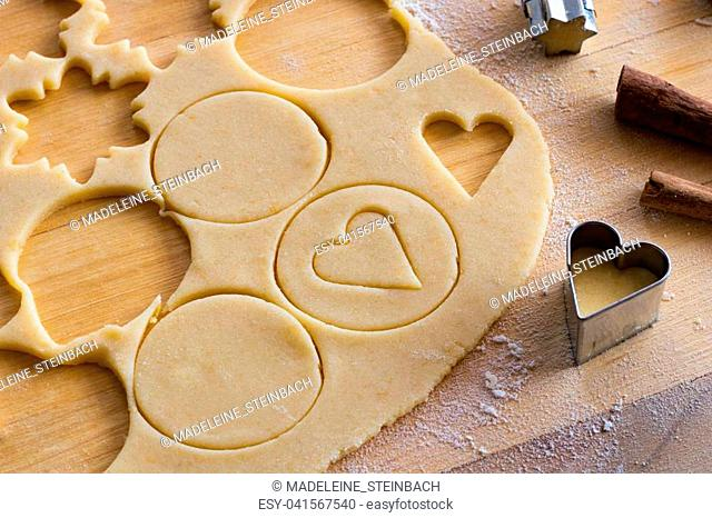 Preparation of traditional Linzer Christmas cookies - cutting out shapes from rolled out dough