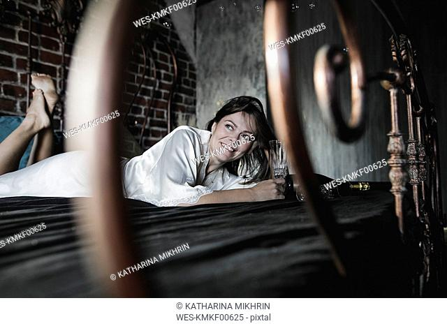 Smiling woman lying on bed holding champagne glass