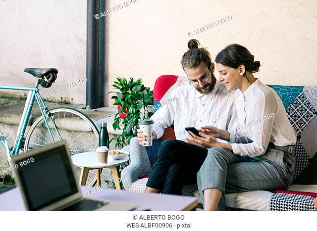 Young couple sitting on a sofa using a smartphone