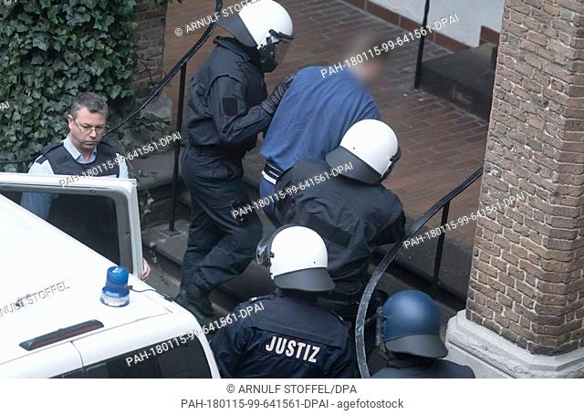 Judicial officers escort a defendant accused of hostage-taking, grievous bodily harm and attempted bodily harm into the district court in Kleve, Germany