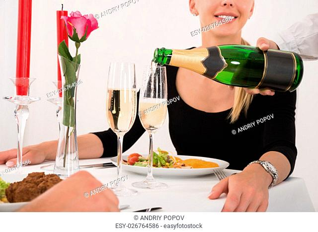 Closeup Photo Of Female Waitress Pouring Champagne Into Glass For Happy Young Couple In Restaurant