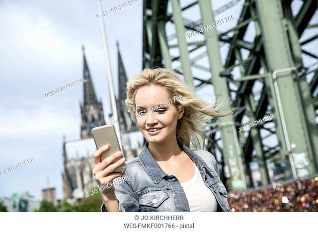 Germany, Cologne, young woman with smartphone on Hohenzollern Bridge