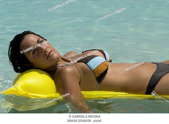 Hispanic woman laying on float in water
