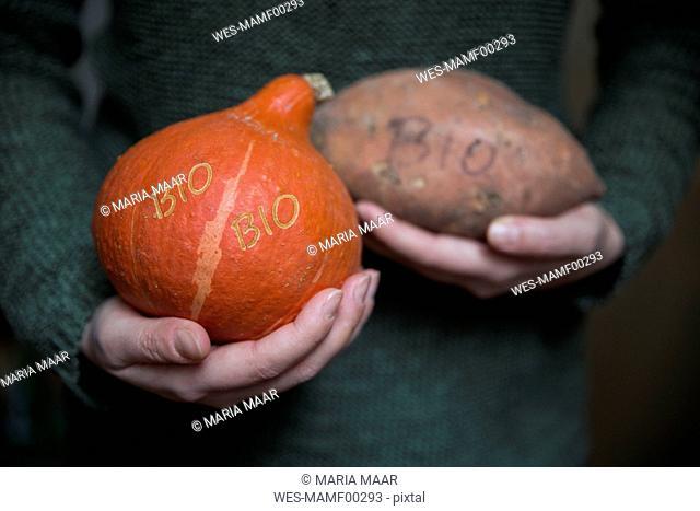 Woman's hands holding organic Hokkaido pumpkin and sweet potatoe with Smart Branding