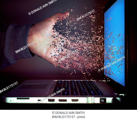 Pixelated hand of Caucasian man dissolving into laptop screen