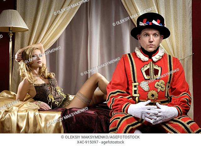 Yeomen of the Guard - Beefeater with stupefied expression on his face sitting on a side of a bed near a beautiful young lady