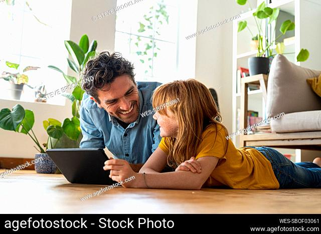 Smiling daughter with digital tablet looking at father while lying on floor in living room at home