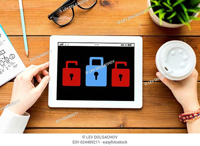 business, education, technology, people and cyber protection concept - close up of woman with lock icon on tablet pc computer screen and coffee on wooden table