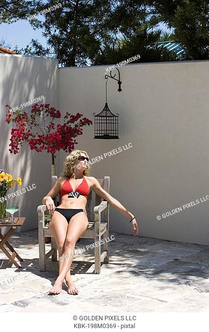Young woman wearing bikini relaxing in a wooden chair