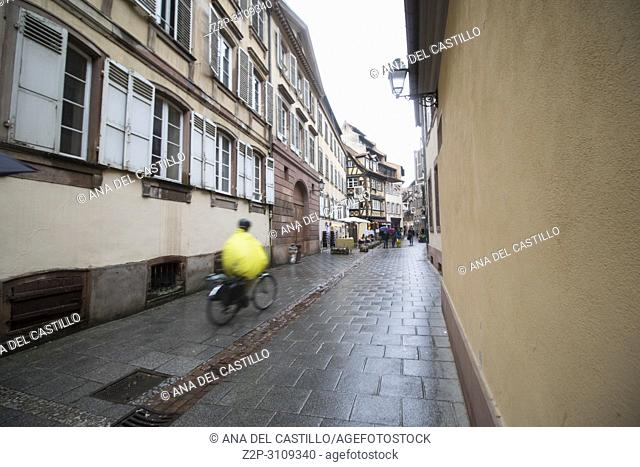Cityscape in Strasbourg on May 12, 2016 in Alsace France. Biker in yellow cycling on a wet street