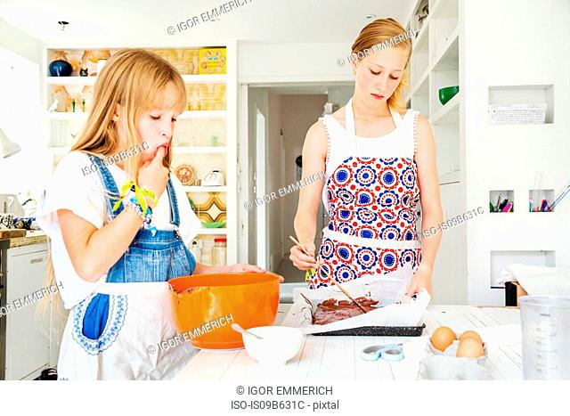 Girls preparing chocolate brownies in kitchen