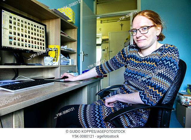 Roosendaal, Netherlands. Young woman working at home, using her desktop computer to upload and manage her photo's on the Dreamstime microstock website