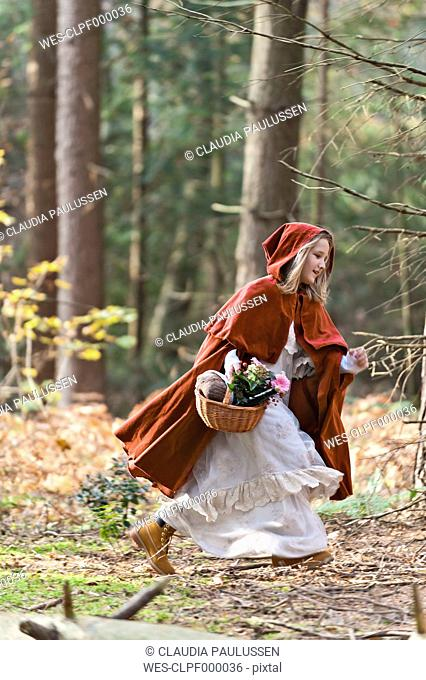 Girl masquerade as Red Riding Hood riunning in the wood