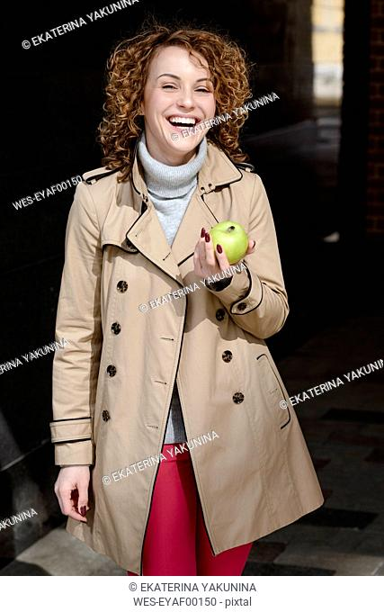 Portrait of laughing woman with green apple wearing beige trenchcoat and turtleneck pullover