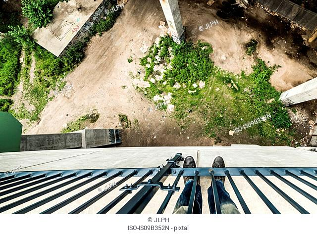 Man standing on Manhattan overpass near Hudson, looking over edge, overhead view, New York City, USA