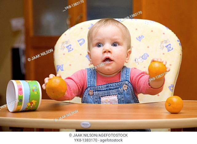 Happy Eight Month Old Infant Girl with Oranges in High Chair