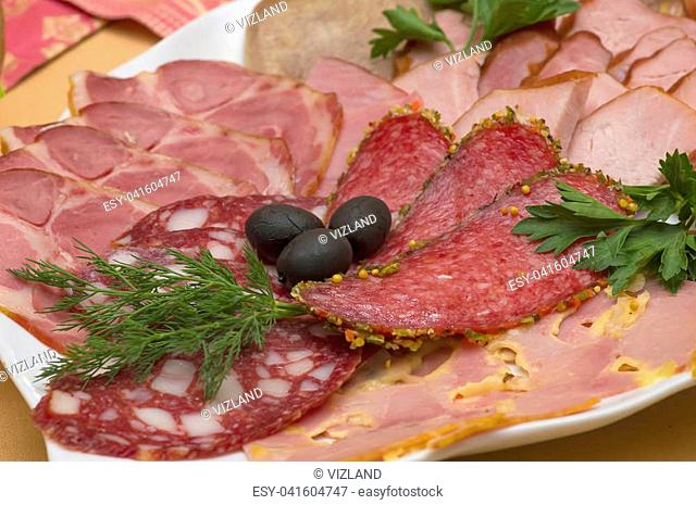 Different meat delicacies in a plate on a server table close-up. Cutting of different types of sausage and meat, decorated with olives and greens