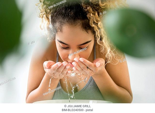 Mixed Race woman splashing water on face