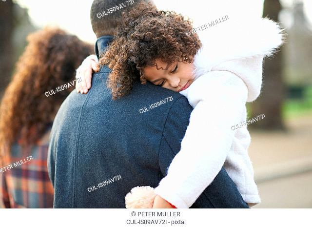 Rear view of father carrying sleeping daughter
