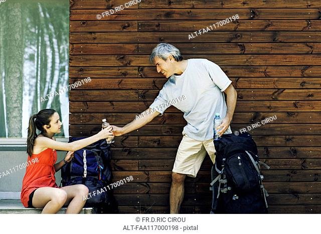 Father giving water bottle to his daughter
