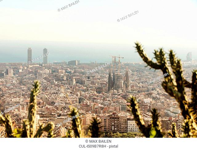 Elevated cityscape view with La Sagrada Familia and distant coast, Barcelona, Spain