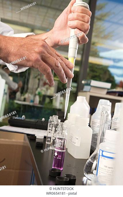 Scientist using a calibrated pipette with sample bottles in the laboratory of water treatment plant