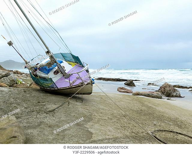 A small yacht, driven ashore onto a rocky beach during a raging storm. Too costly to remove as it's hemmed in by beach houses on one side and rocks on the other...