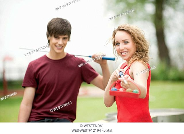Germany, Bavaria, Ammersee, Young couple, man holding pool cue, smiling, portrait