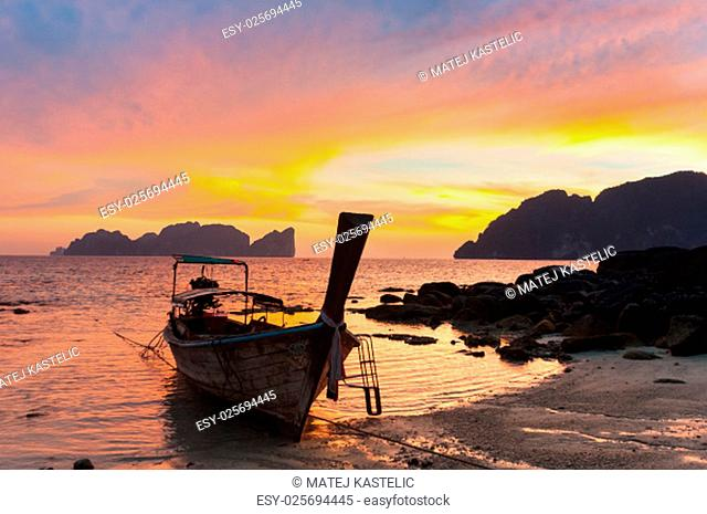 Traditional thai wooden longtail boat on beach of Phi-Phi Don island in sunset. Silhouette of famous Phi Phi Lee island in background