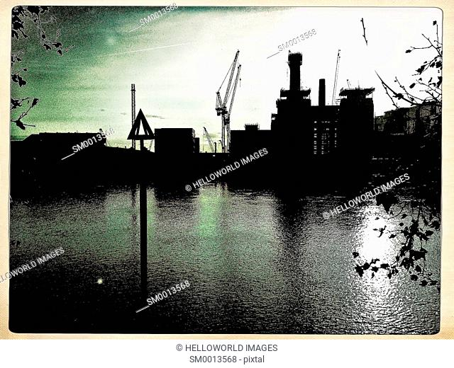 Battersea Power Station development and water level marker silhouetted, London, England