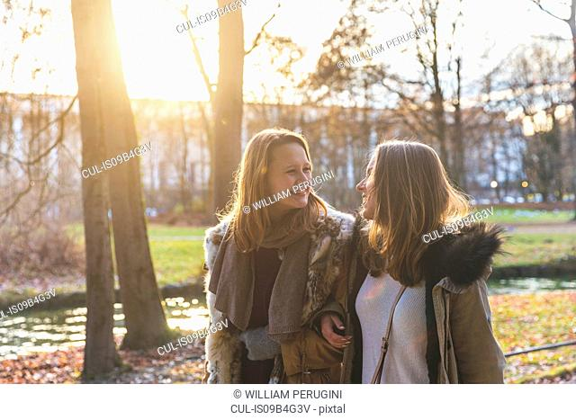 Two young female friends strolling on park riverside