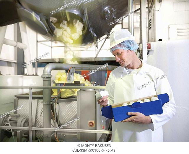 Worker inspecting goat's butter in dairy