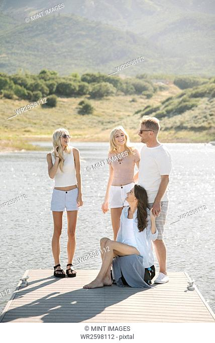 Man, woman and their two blond daughters standing on a jetty