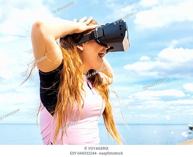 Young woman testing VR eyeglasses outside. Female wearing virtual reality headset during summer weather