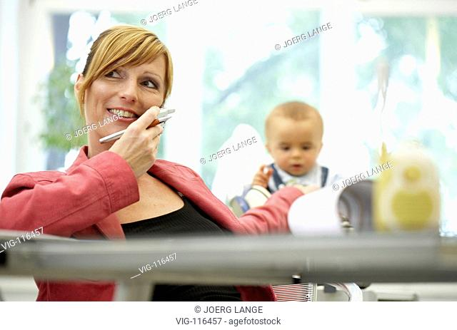 A business woman works at her bureau. Behind her a baby sits in a Max-Cosy. - DRESDEN, GERMANY, 23/08/2005