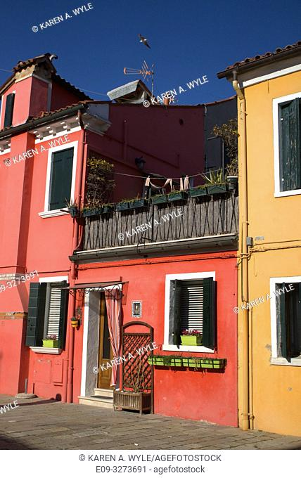 brightly colored buildings (salmon and orange-yellow) and deep blue sky, seagull flying over, island of Burano, near Venice, Italy