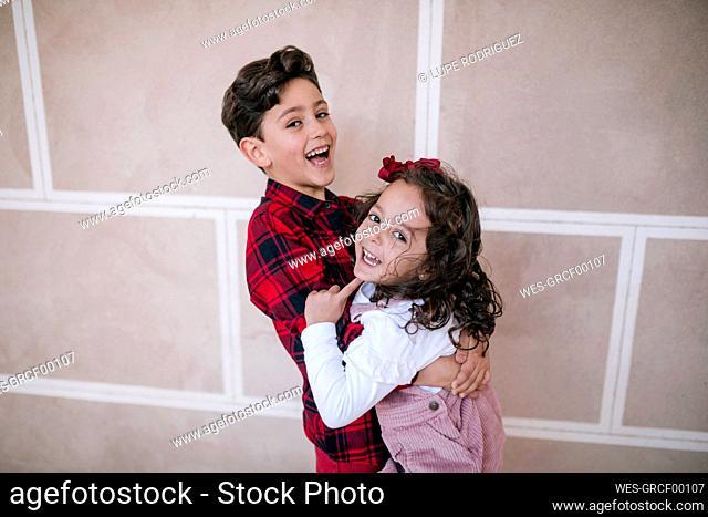 Happy boy cuddling with girl at a wall
