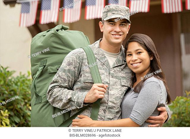Soldier and girlfriend smiling outdoors
