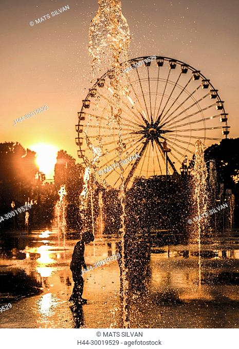 Child Playing in Fountain with Ferris Wheel and in Sunset in Nice In Provence-Alpes-Côte d'Azur, France