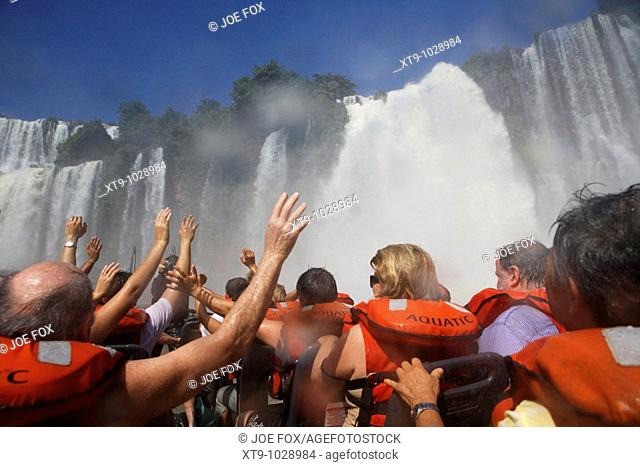 group of tourists getting soaked on speedboat underneath the mbigua fall waterfalls iguazu national park, republic of argentina, south america