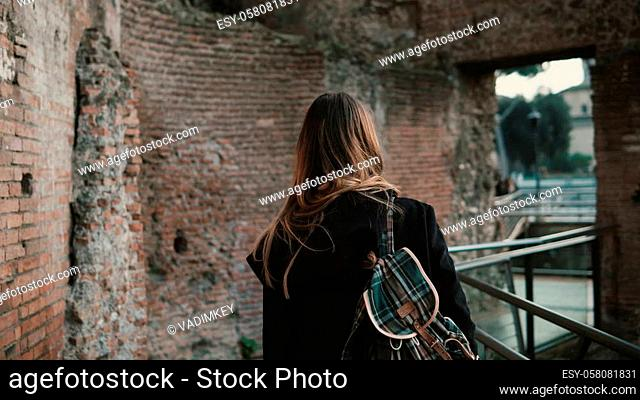Young woman going through Roman Forum in Rome, Italy. The girl is capturing the beauty of old walls and enjoying the view on other authentic and antique...