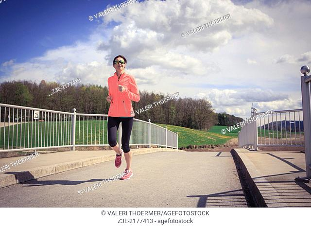 a woman jogging through the rural landscape near Coburg, Germany
