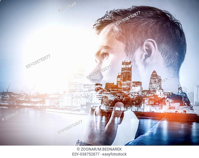 Young businessman thinking. Double exposure city background