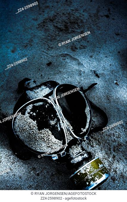 Dark blue photo of a nighttime vintage gas mask lying on sand. Cold war casualties