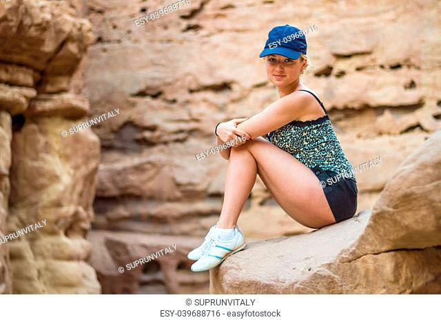 Beautiful girl sitting on a rock in Red Canyon. Israel