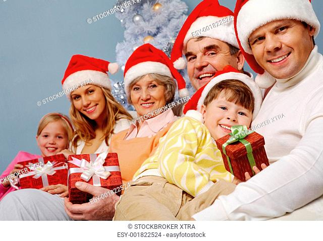 Portrait of happy family in Santa caps with affectionate boy holding giftbox with his father near by