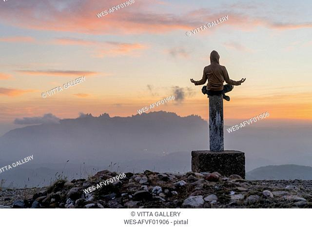 Spain, Barcelona, Natural Park of Sant Llorenc, man sitting in yoga pose on pole at sunset