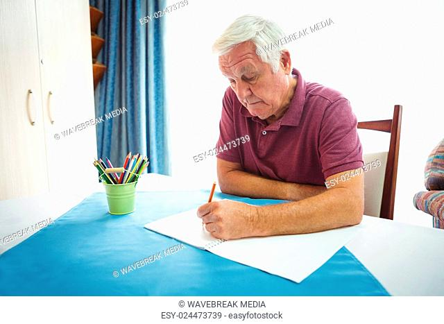 Portrait of retired man writing on white paper