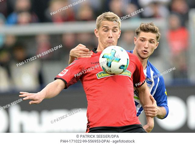 Freiburg's Nils Petersen (L) and Berlin's Niklas Stark (R) vying for the ball during the German Bundesliga soccer match between SC Freiburg and Hertha BSC in...